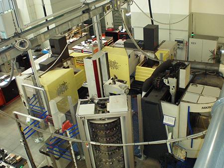 La cella è un sistema di lavorazioni integrate che comprende al suo interno una fresa a cinque assi per la fresatura degli elettrodi in grafite, una macchina di misura con funzionalità di pre-setting degli elettrodi stessi e due macchine di elettroerosione a tuffo, il tutto asservito da un robot.