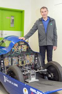Philippe Maindru, che insegna nel corso professionale per tecnico superiore in ambito di motori a combustione interna, si trova vicino all'auto elettrica Microjoule