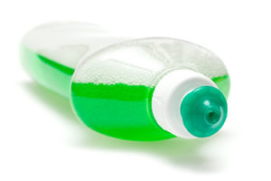 Lying bottle of green bubbling dish liquid isolated on a white background.